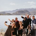 A group of people taking a selfie in front of lake bled